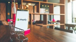 Image of a shopping cart toy on a wooden desk carrying a mobile phone that features the Shopy (SHOP) logo on it