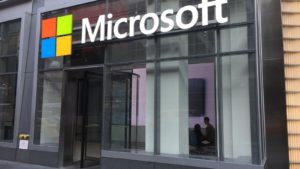 Image of corporate building with Microsoft (MSFT) logo above the entrance. tech stocks