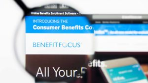A magnifying glass zooms in on the Benefitfocus (BNFT) website.