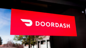 Close up of Doordash logo and symbol displayed at the entrance to one of their offices