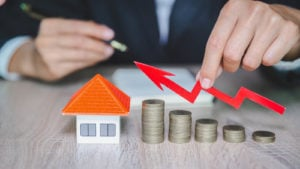a stack of coins and red arrow pointing up to a house figure to represent crowdfunding real estate