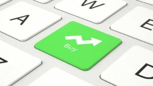 "a green button on a keyboard has an arrow pointing upward with the word ""Buy"". representing undervalued stocks to buy"