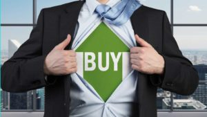 A businessman ripping his shirt off to reveal an upward green arrow with the word buy on it underneath to represent russell 2000 stocks