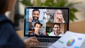 Person Working From Home Having Online Group Videoconference On Laptop