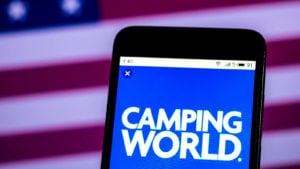 Camping World (CWH) logo on a smartphone in front of an American flag background.