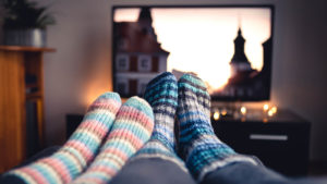 Two pairs of feet in socks in front of a television set