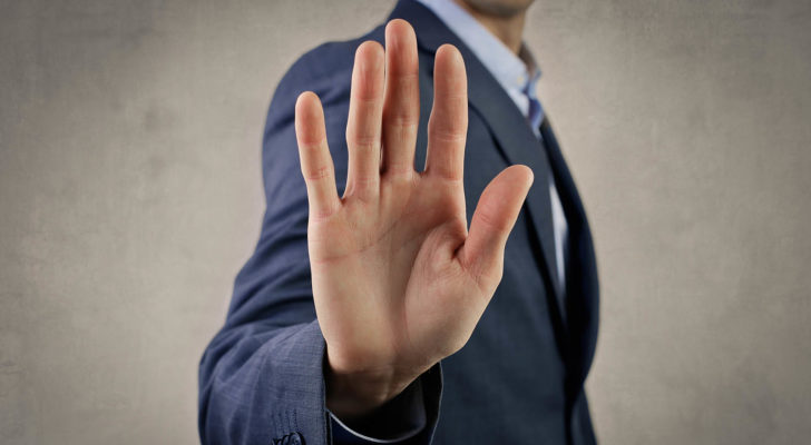 hand of man in suit signaling stop