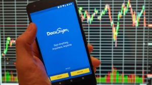 Docusign (DOCU) logo on a phone screen with stock charts in background