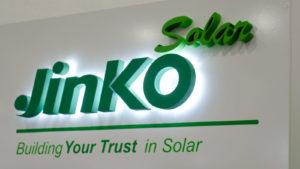 The JinkoSolar (JKS) logo displayed on a plain white wall.