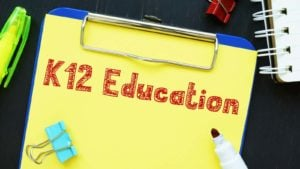 "a clipboard with the words ""k-12 education"" written on a yellow piece of paper and in red marker"
