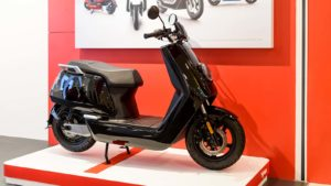A black Niu branded bike on a white showcase floor contrasted with a red wall
