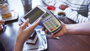 a person holding a smartphone over a check out scanner representing payments stocks to buy