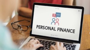 "The phrase ""personal finance"" is displayed on a laptop screen."