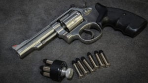 Image of a pistol and several bullets laying on a dark grey surface