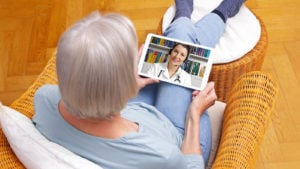 A woman in a wicker chair looking at a doctor on a tablet, chatting.