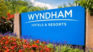 A sign for Wyndham Hotels & Resorts (WH) in bright blue.