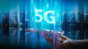 5G digital hologram floating over a phone on a city background.
