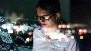 A businesswoman looks at a floating interface screen full of data.