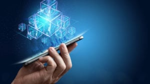 An image of a hand holding a cell phone with several visualizations of digital building blocks floating above it. representing sto platforms