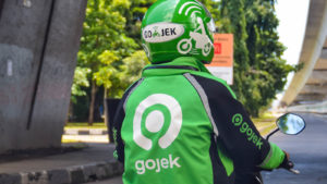A Gojek driver in company helmet and jacket waits at a stoplight.
