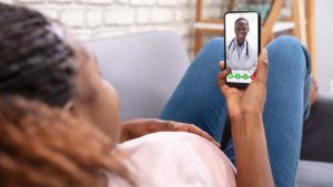 A woman laying back on her couch doing a video visit with a doctor via her smartphone.
