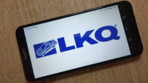 The LKQ Corporation (LKQ) logo is displayed on a smartphone.