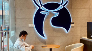 Luckin (LKNCY) logo on the wall of a coffee shop with a customer sitting at a table below it.