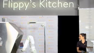 """Flippy' Kitchen"" showing Miso Robotics' burger-flipping robot next to team member."