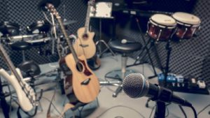 A microphone, drums, and several guitars are in a recording studio. music stocks to buy