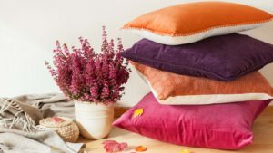 A stack of purple, pink and orange pillows next to some dried autumnal flowers.