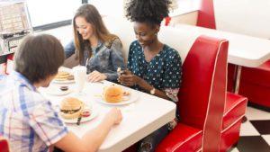 Tres amigos adultos jóvenes se sientan alrededor de un stand de restaurante vintage comiendo hamburguesas.  la imagen representa acciones de restaurantes