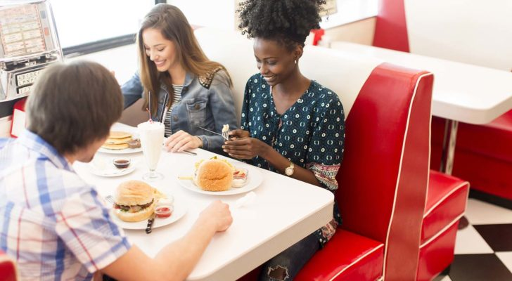 Three young adult friends sit around a vintage restaurant booth eating hamburgers.