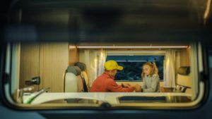 An RV window shows a father and daughter sitting at the RV table.