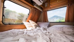 The inside of a camper van with a bed and two windows looking outside.