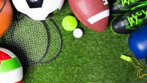 Various sports equipment like a football, soccer ball and volleyball on green grass.