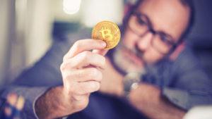homme avec des lunettes tenant une pièce avec le logo Bitcoin (BTC-USD)