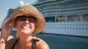 A close-up shot of a woman wearing a straw hat with a cruise ship in the background.