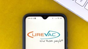 The logo for CureVac (CVAC) is displayed on a smartphone screen over a yellow background.