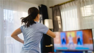 View from behind of woman working out to a televised exercise program.