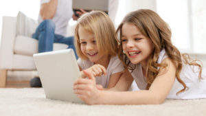 An image of two young girls looking at a tablet and smiling while an adult reads in the background.