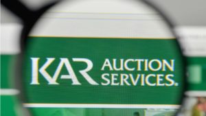 A magnifying glass zooms in on the website of KAR Auction Services (KAR).