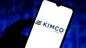 The Kimco Realty (KIM) logo displayed on a smartphone screen. Real Estate Stocks