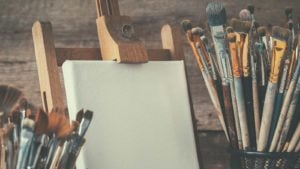 A wooden easel holds a white canvas and is surrounded by bins of different size paintbrushes.