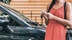 A woman hails a ride through her mobile phone.
