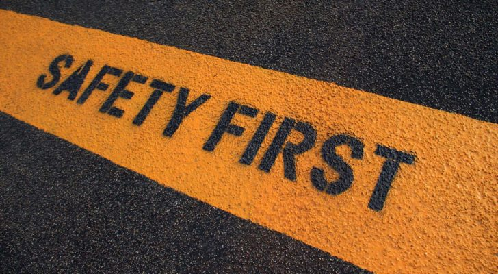 Safety First painted on a yellow caution strip on dark pavement.