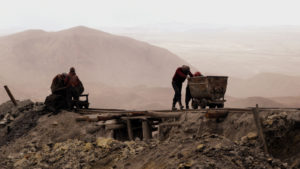 Mine workers pushing carts in mountainous region.