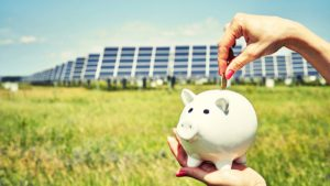 Piggy bank in front of solar panel infrastructure