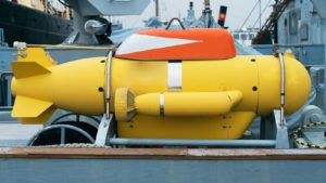 A bright yellow unmanned underwater vehicle on a ship.