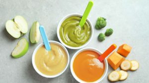 An image from above three cups of baby food, with little bites of vegetables scattered around them.