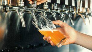 Une photo d'une personne versant une bière d'un robinet.